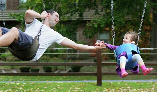 Jacob Raphael of Albany, left, holds hands with his daughter Ella Raphael, 2, as they swing together on Wednesday, Oct. 15, 2014, at Buckingham Pond in Albany, N.Y. (Cindy Schultz / Times Union) Photo: Cindy Schultz