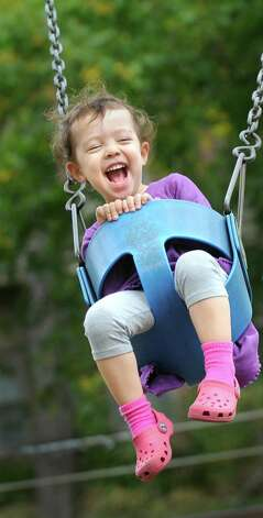 Ella Raphael, 2, of Albany is full of joy as she swings, with the help of her father Jacob Raphael, on Wednesday, Oct. 15, 2014, at Buckingham Pond in Albany, N.Y. (Cindy Schultz / Times Union) Photo: Cindy Schultz