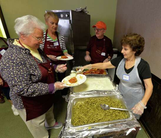 Volunteers serve food at the St. John's/St. Ann's Outreach soup kitchen in the former Albany Fire Department Engine 5 building Tuesday afternoon Oct. 14, 2014 in Albany, N.Y.  (Skip Dickstein/Times Union) Photo: SKIP DICKSTEIN / 10029007A
