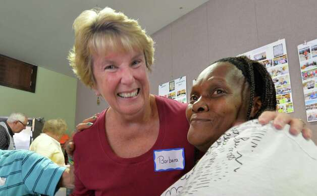 Barbara Quinn, left enjoys a happy moment with Faysha Tume at the St. John's/St. Ann's Outreach soup kitchen in the former Albany Fire Department Engine 5 building Tuesday afternoon Oct. 14, 2014 in Albany, N.Y.  (Skip Dickstein/Times Union) Photo: SKIP DICKSTEIN / 10029007A