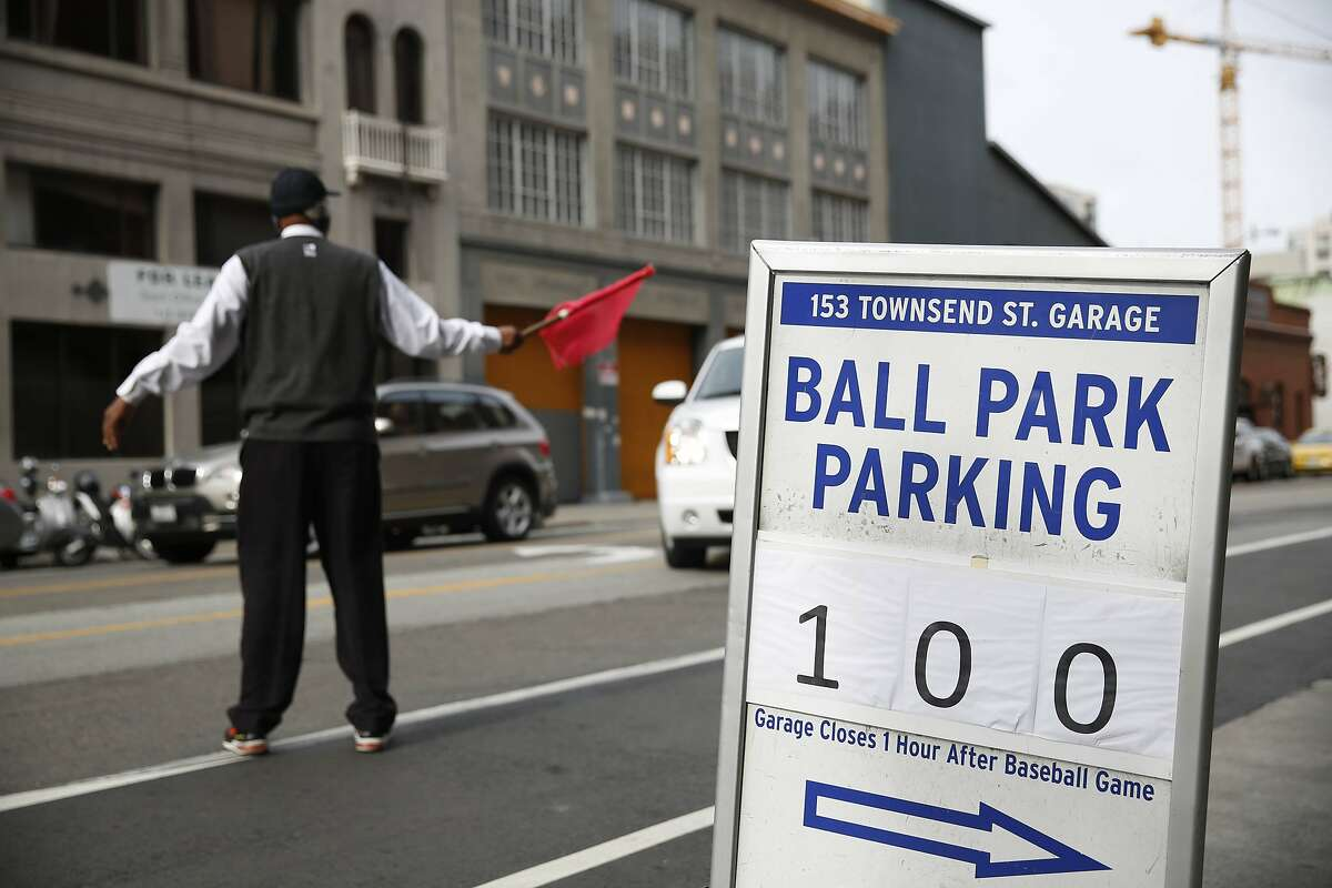 A man waves a red flag next to a sign for $100 ball park parking along Townsend Street on Wednesday, October 15, 2014 in San Francisco, Calif.
