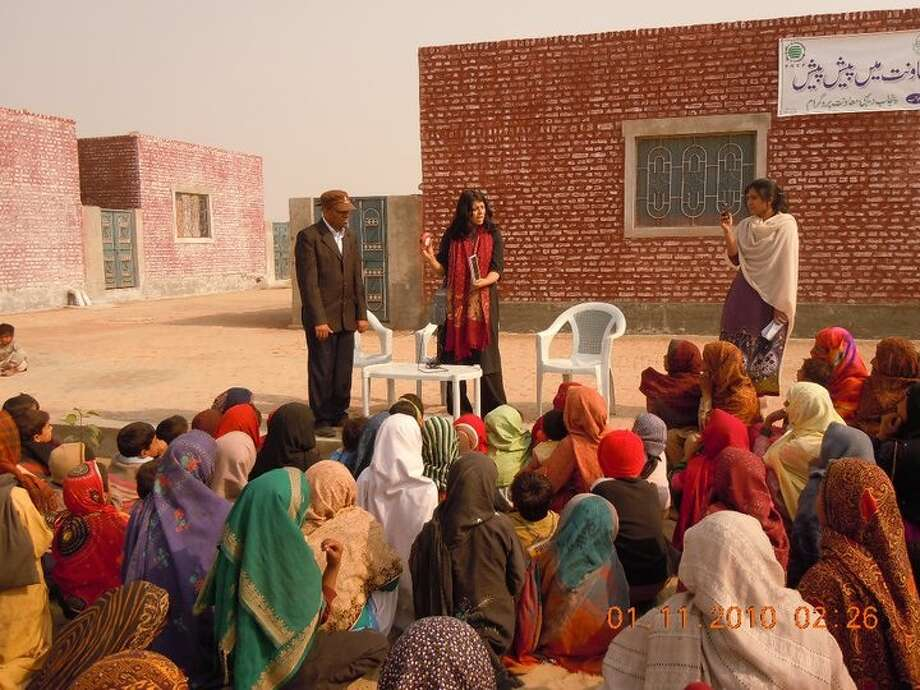 Shazia Khan with EcoEnergy Advisor Ayesha Ahsan Malik demonstrating the power of solar lighting to rural women outside Multan, Punjab, Pakistan. Photo provided by Shazia Khan.