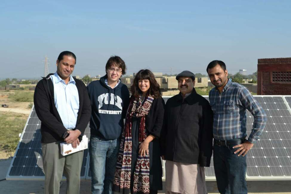 Shazia Khan and EcoEnergy management team with Abrar Khan at solar panels in Badin, Sindh, Pakistan. Photo provided by Shazia Khan.