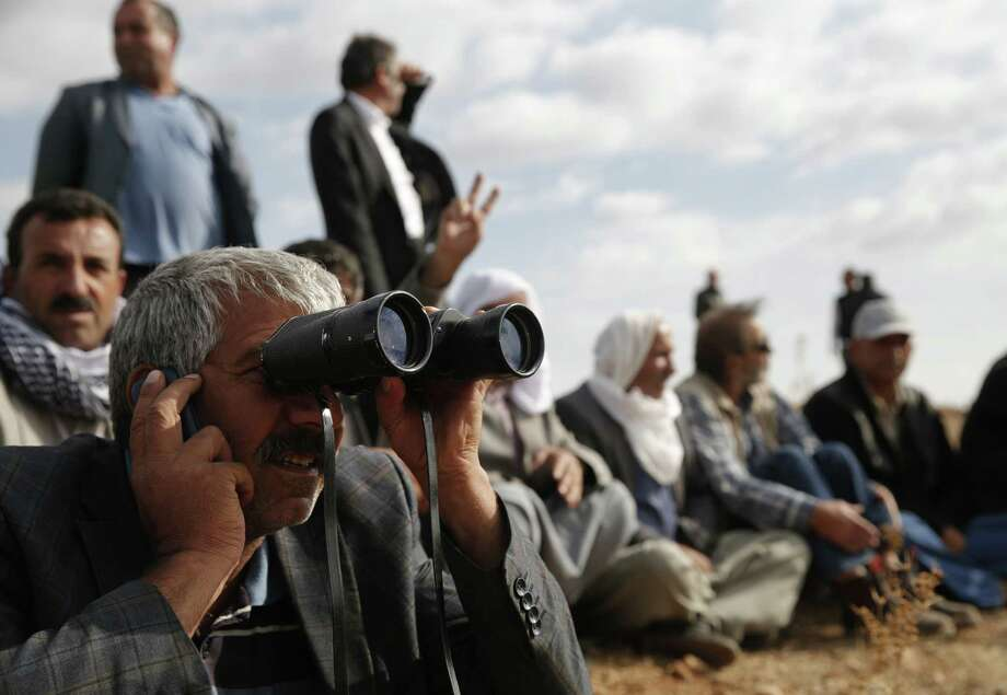 People gather on a hilltop on the outskirts of Suruc, Turkey, at the Turkey-Syria border, to watch fighting between Syrian Kurds and ISIS militants in Kobani, Syria. Photo: Lefteris Pitarakis / Associated Press / AP