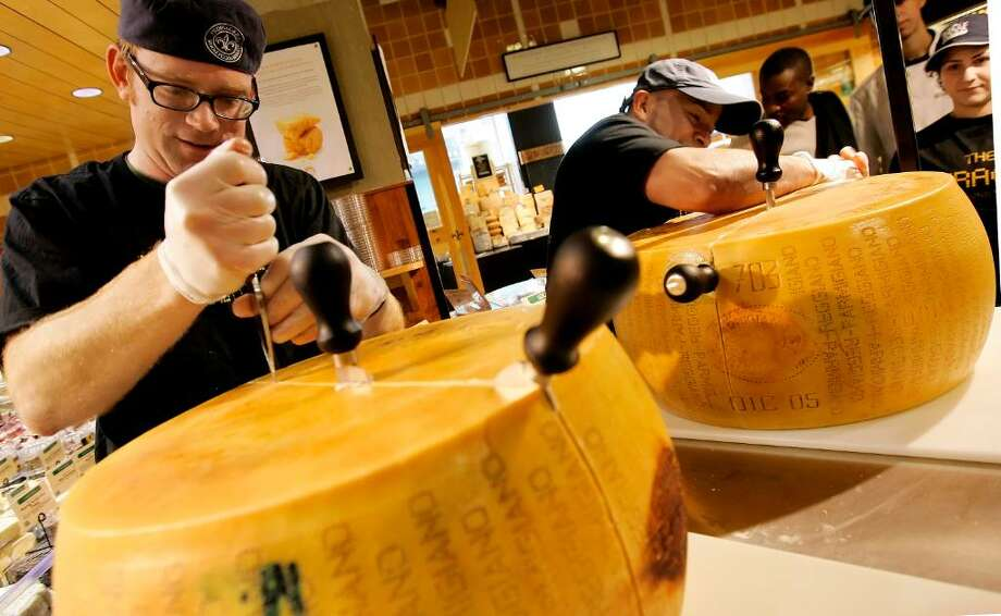 """Photos from 2008, when, with nearly 300 wheels opened at 176 Whole Foods Market stores, the chain set a Guinness World Record for """"Most Parmigiano Reggiano Wheels Cracked Simultaneously."""" Whole Foods will attempt to outdo that record this year.   Using traditional methods and the official 5-piece knife set from Italy's Consorzio del Formaggio Parmigiano Reggiano, the process of cracking into an 85-pound wheel requires an expert hand and usually takes about half an hour. Photo: Contributed Photo / Connecticut Post Contributed"""