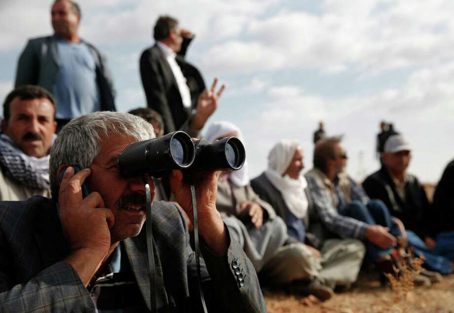 People gather on a hilltop on the outskirts of Suruc, at the Turkey-Syria border, to watch fighting between Syrian Kurds and the militants of Islamic State group in Kobani, Syria, over the border, Wednesday, Oct. 15, 2014. Kobani, also known as Ayn Arab, and its surrounding areas, has been under assault by extremists of the Islamic State group since mid-September and is being defended by Kurdish fighters. (AP Photo/Lefteris Pitarakis) ORG XMIT: AXLP113 Photo: Lefteris Pitarakis / AP