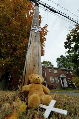 A a teddy bear, crucifix and a white ribbon sit across the street from the murder scene Wednesday afternoon Oct. 15, 2014 in Guilderland, N.Y.   (Skip Dickstein/Times Union) Photo: SKIP DICKSTEIN