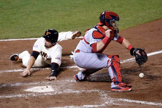 San Francisco's Juan Perez scores as St. Louis catcher Tony Cruz can't field the ball in the sixth inning at AT&T Park. The Giants lead the NLCS 3-1. Photo: Thearon W. Henderson / Getty Images / 2014 Getty Images