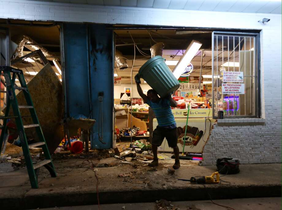 Houston police are investigating a smash-and-grab theft at the Phillips 66 gas station at 7701 West Montgomery Road. An employee, cleaning up the mess, says an ATM was stolen. Photo: Gary Coronado / Houston Chronicle