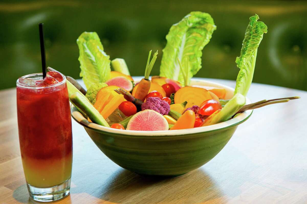 A Root & Remedy, containing beet, carrot, ginger, turmeric and honey lemonade, left, is paired with the Vegetable Crudite at True Food.