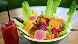 A Root & Remedy, containing Beet, Carrot, Ginger, Turmeric & Honey Lemonade, left, is seen with the Vegetable Crudité, right, at True Food Kitchen, Wednesday, Oct. 15, 2014, in Houston. (Cody Duty / Houston Chronicle)
