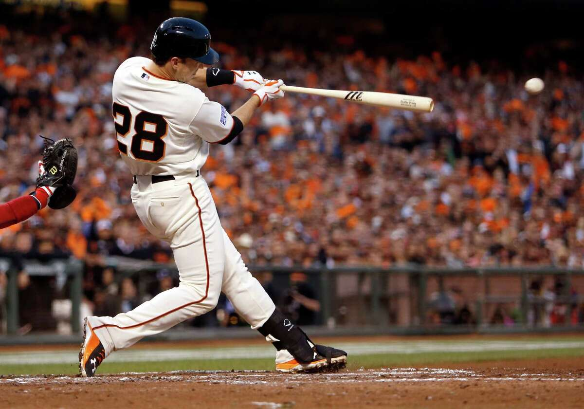 Giants Buster Posey singles in the third inning to score Joaquin Arias during Game 4 of the NLCS at AT&T Park on Wednesday, Oct. 15, 2014 in San Francisco, Calif.