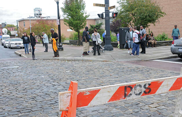 People gather on a corner as police block off South Pearl Street between Schuyler and Bassett Streets as officers investigate a shooting of a male victim there on Thursday, Oct. 16, 2014 in Albany, N.Y.  (Lori Van Buren / Times Union) Photo: Lori Van Buren