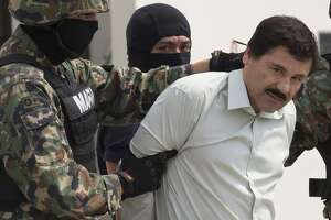 """Drug trafficker Joaquin """"El Chapo"""" Guzman is escorted to a helicopter by Mexican security forces at Mexico's International Airport in Mexico city, Mexico, on Saturday, Feb. 22, 2014. Mexico's apprehension of the world's most-wanted drug boss struck a blow to a cartel that local and U.S. authorities say swelled into a multinational empire, fueling killings around the world. Photographer: Susana Gonzalez/Bloomberg *** Local Caption *** Joaquin Guzman"""