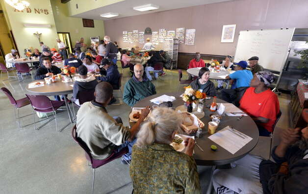 Clients enjoy a free lunch around round tables at the St. John's/St. Ann's Outreach Center soup kitchen Tuesday. (Skip Dickstein/Times Union)
