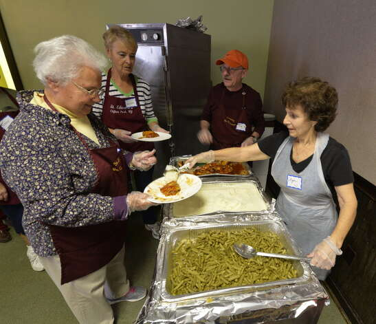 Volunteers serve food at the St. John's/St. Ann's Outreach Center Welcome Table Tuesday. (Skip Dickstein/Times Union)