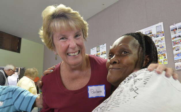 Barbara Quinn, left, enjoys a happy moment with Faysha Tume at the St. John's/St. Ann's Outreach Center Welcome Table Tuesday. (Skip Dickstein/Times Union)