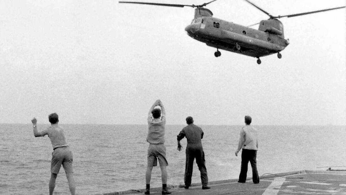 Aboard the USSKirk, crew members signal a Chinook to drop its passengers, those evacuating Saigon, on the deck on April 29, 1975.