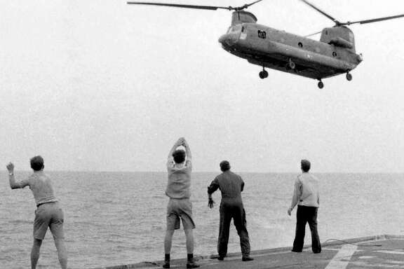 Aboard the USS	Kirk, crew members signal a Chinook to drop its passengers, those evacuating Saigon, on the deck on April 29, 1975.