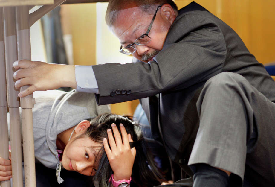 """Sixth grader Lily Lin shared her space under her desk with San Francisco Mayor Ed Lee during the earthquake drill Thursday October 16, 2014. The great California """"Shakeout"""" was observed at Marina Middle School in San Francisco, Calif. with an earthquake drill for students and some public officials. Photo: Brant Ward / The Chronicle / ONLINE_YES"""