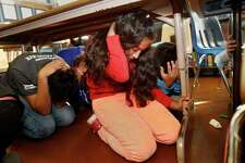 Sixth grader Naomi Holmes (right) and her classmates slide under their classroom tables for the earthquake drill.