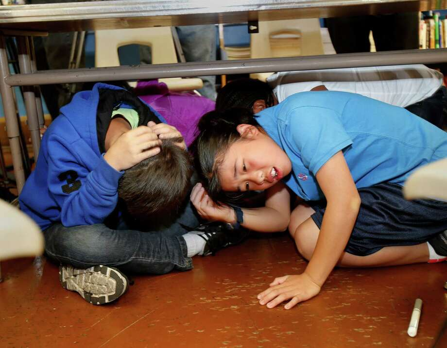 """Sixth graders Susan Li (right) and her classmate Victor Ruan ducked under their classroom table for the earthquake drill Thursday October 16, 2014. The great California """"Shakeout"""" was observed at Marina Middle School in San Francisco, Calif. with an earthquake drill for students and some public officials. Photo: Brant Ward / The Chronicle / ONLINE_YES"""