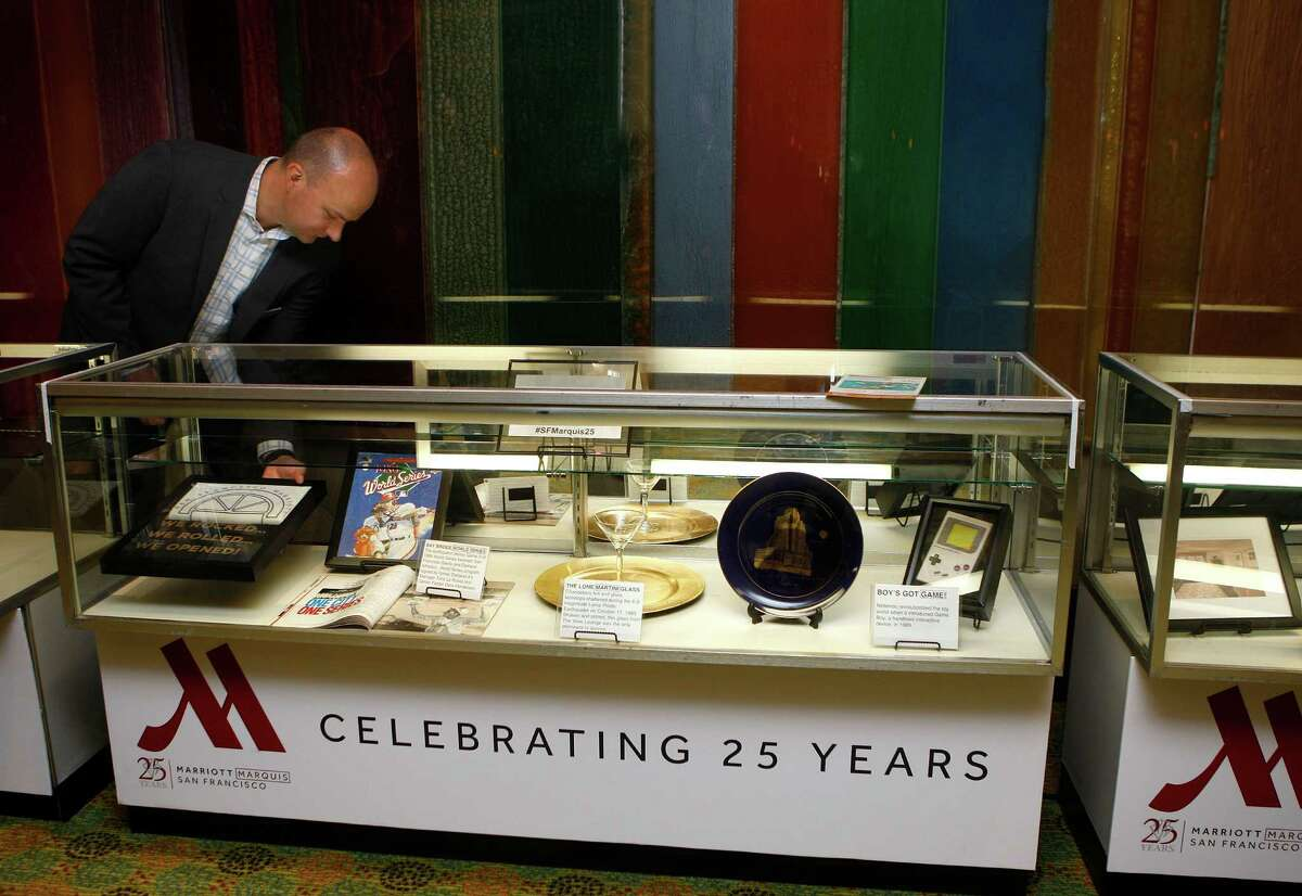 Director of sales and marketing Frank Manchen places framed t-shirts in a historic display case on the first floor of the Marriott hotel in San Francisco, Calif., on Wednesday, October 15, 2014. Printed t-shirts were given to hotel staff 72 hours after the 1989 Loma Prieta earthquake.