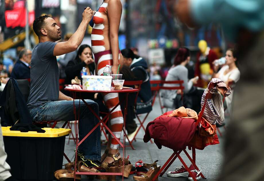 BANNER DAY AT THE BISTRO: A patriot has her body painted in stars and stripes in New York. Photo: Jewel Samad, AFP/Getty Images