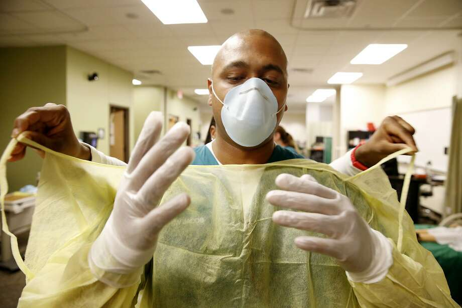 Mathew Jacob, a maternal newborn nursing student, has help removing a gown during a refresher course on personal protective equipment procedure taught at the Brookhaven College School of Nursing in Farmers Branch, Texas, Tuesday Oct. 14, 2014. Nursing, EMS and radiological sciences students will all take the refresh course.  A second Dallas hospital worker has tested positive for Ebola, pointing to lapses beyond how one individual may have donned and removed personal protective garb. Photo: Andy Jacobsohn, Associated Press