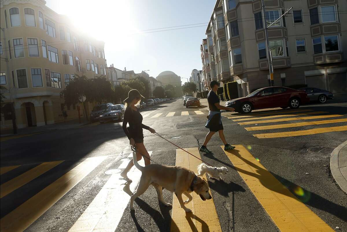 Mike and Cathy Posey walk their dogs Oliver and Olivia on Divisadero Street at Beach Street in the Marina District of San Francisco on October 12, 2014.