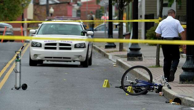 Crime scene tape, a bicycle, an oxygen tank and evidence markers are all that remains after a shooting in front of the Rite Aid Pharmacy Thursday morning Oct. 16, 2014 in Albany, N.Y.     (Skip Dickstein/Times Union) Photo: SKIP DICKSTEIN