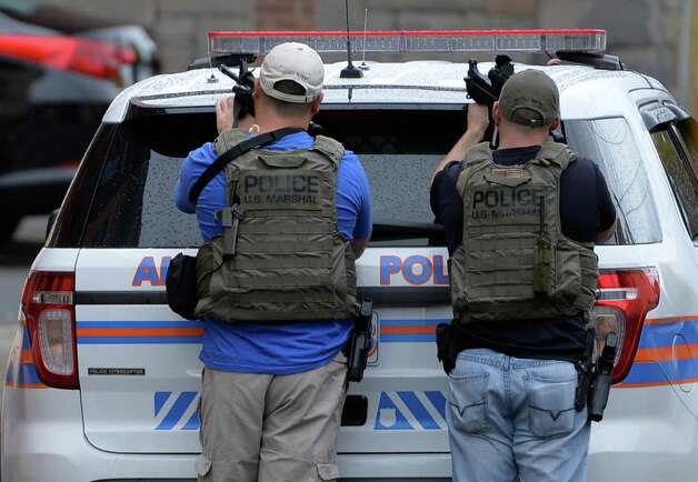 Members of the U. S. Marshalls join the Albany Police as they prepare to search 70 Basset Street  for a shooting suspect Thursday afternoon Oct. 16, 2014 in Albany, N.Y.     (Skip Dickstein/Times Union) Photo: SKIP DICKSTEIN