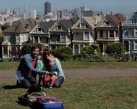 Jesse (left) and Stephanie Smith pull the kids, Josslyn and Eli in for a family photo in front of the Painted Ladies at Alamo Square. A nice place to walk through on the way to brunch.
