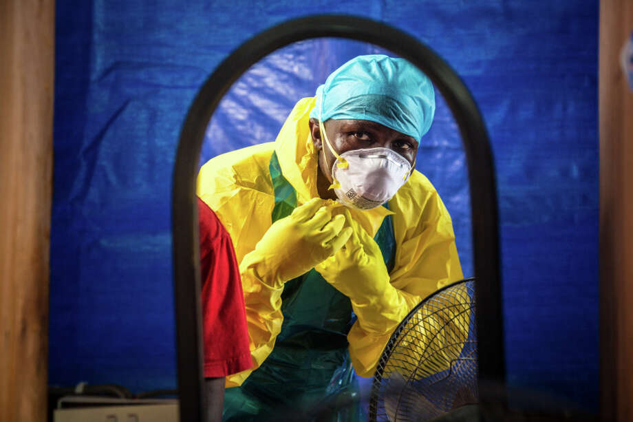 A healthcare worker dons protective gear before entering into an Ebola treatment center in the west of Freetown, Sierra Leone. Photo: Michael Duff / Associated Press / AP