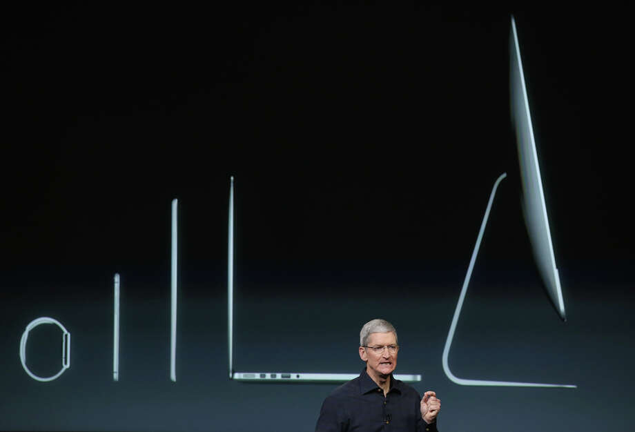 With Apple products shown behind him, CEO Tim Cook speaks during an event introducing new iPads. Photo: Justin Sullivan / Getty Images / 2014 Getty Images