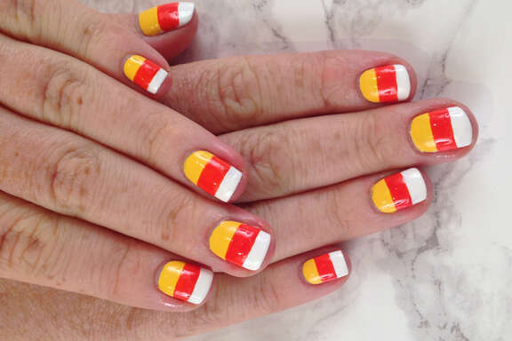 Candy corn-inspired Halloween nail art by TopCoat nail artist Taylor Watson of SF Party Nails: White Matter by Formula X Nail Polish, Monarch by RGB Cosmetics, Pimms by Butter London.