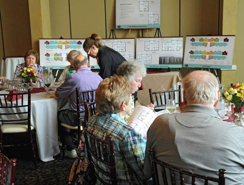 Potential clients of the proposed Glenmont Abbey Village, an apartment community targeting residents 55 and over, look over site literature on Thursday, Oct. 16, 2014 in Delmar, N.Y. The informational luncheon took place at Normanside Country Club. (Lori Van Buren / Times Union)