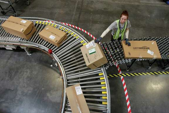 FILE - In this Nov. 11, 2010, file photo, Katherine Braun sorts packages toward the right shipping area at an Amazon.com fulfillment center in Goodyear, Ariz. Amazon is hiring 80,000 seasonal workers for its distribution centers as it looks to improve its shipping efficiency during the crucial 2014 holiday season. (AP Photo/Ross D. Franklin, File)