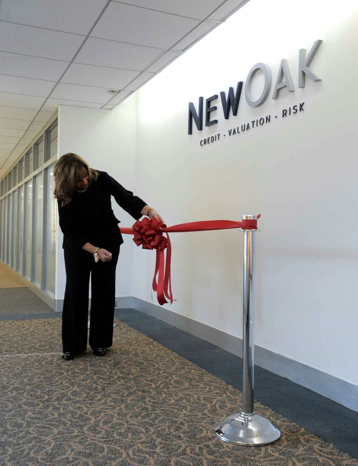Diane Disher, a Sales Manager for the Matrix Corporate Center, arranges a ribbon under for the New York City based finance company NewOak, which held a reception and ribbon cutting for their new Danbury, Conn, office at the Matrix Corporate Center, in Danbury, Conn, on Thursday, October 16, 2014.