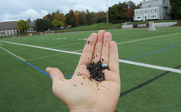 Close up of the black bead like material in the artificial turf of the football field at Union College on Thursday, Oct. 16, 2014 in Schenectady, N.Y. There are studies going on about a potential link with this substance causing cancer.  (Lori Van Buren / Times Union) Photo: Lori Van Buren
