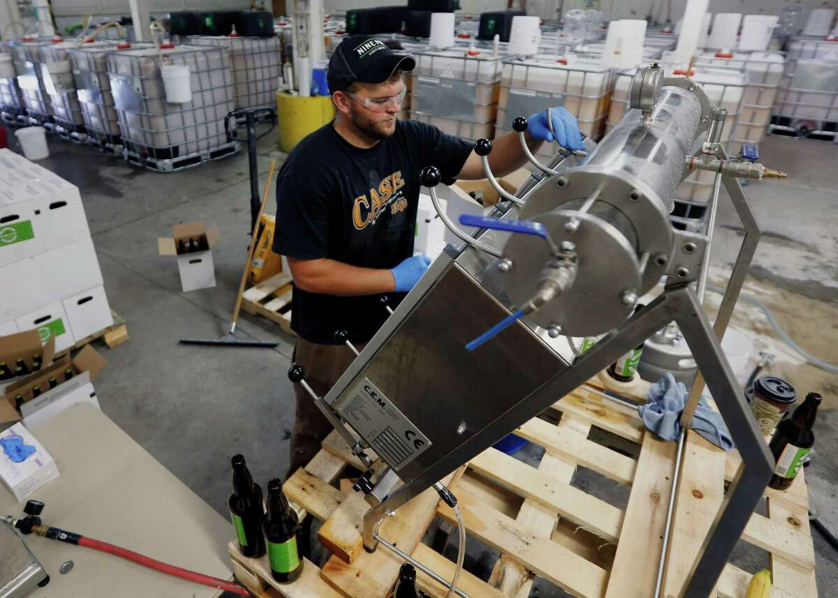 In this Oct. 3, 2014 photo, Mitch Rogers bottles hard cider at Nine Pin Cider Works in Albany, N.Y. Apple growers are tapping into the hard cider revenue stream after sales of hard cider in the U.S. have tripled over the last three years to $1.3 billion in 2013. (AP Photo/Mike Groll) ORG XMIT: NYMG201