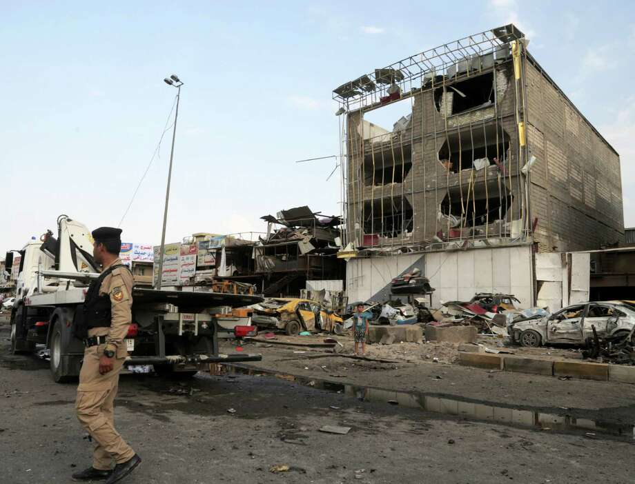 Security forces inspect the site of a car bomb explosion in the largely Shiite eastern neighborhood of Talibiyah in Baghdad. Photo: Khalid Mohammed / Associated Press / AP