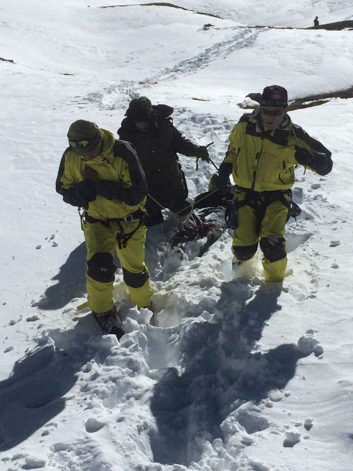 In a handout photo, Nepalese army soldiers drag a corpse down from the Thorong La pass near Muktinath, Nepal, Oct. 16, 2014. Some 350 hikers were crossing Thorong La when a freak snowstorm struck on Tuesday. At least 27 are confirmed dead and the number expected to rise N perhaps dramatically N as frozen bodies are uncovered from several feet of snow. (Nepalese Army via The New York Times) -- FOR EDITORIAL USE ONLY. ORG XMIT: XNYT143 Photo: NEPALESE ARMY / NEPALESE ARMY
