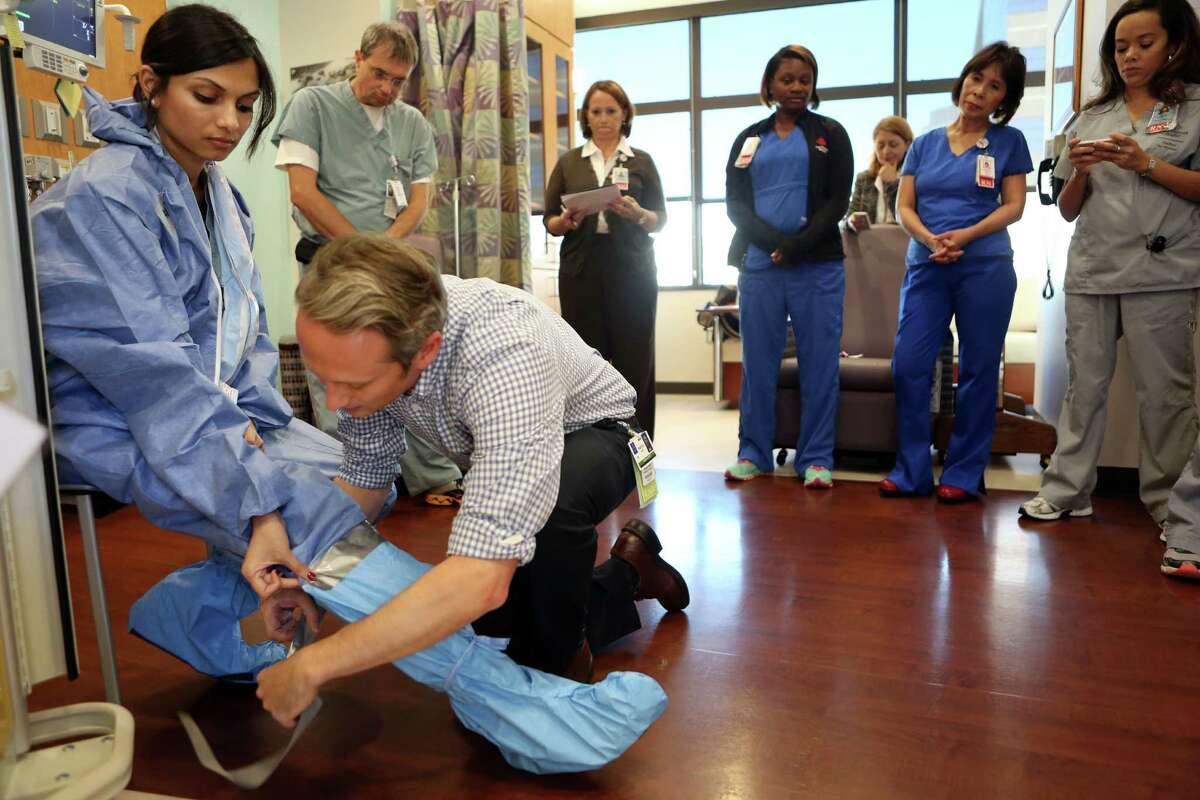Drs. Shweta Parmekar and Brent Kaziny demonstrate safety gear Thursday at Texas Children's Hospital.