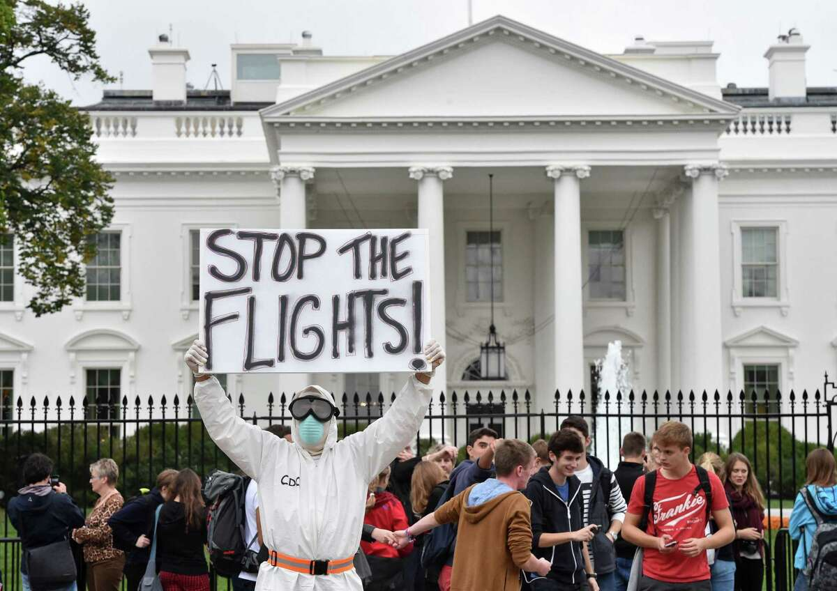 A protester garbed in a hazmat suit and mask demands a halt to flights from West Africa outside the White House on Thursday.