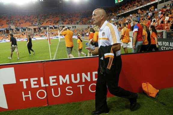 Houston Dynamo's head coach Dominic Kinnear walks out on the field before the start of an MLS soccer match at BBVA Compass Stadium, Thursday, Oct. 16, 2014, in Houston.