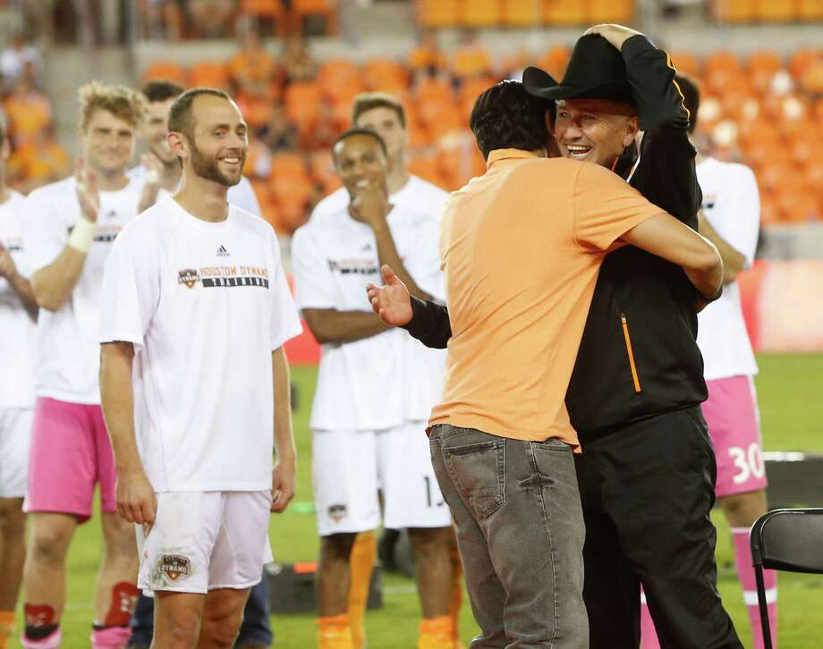 Don't let the man-in-black outfit fool you. Dominic Kinnear is the good guy Thursday night at BBVA Compass Stadium as the coach is hugged by former player Brian Ching. Brad Davis, left, and the rest of the Dynamo await their turn to salute Kinnear. Photo: Karen Warren, Staff / © 2014 Houston Chronicle