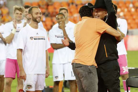 Don't let the man-in-black outfit fool you. Dominic Kinnear is the good guy Thursday night at BBVA Compass Stadium as the coach is hugged by former player Brian Ching. Brad Davis, left, and the rest of the Dynamo await their turn to salute Kinnear.