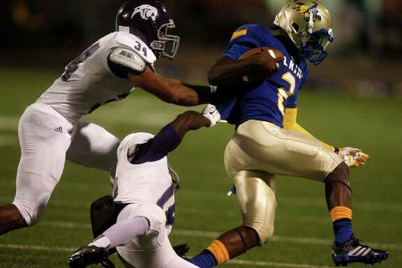 Elkins quarterback Jonathan Giles (2) is brought down by Ridge Point 's Cameron Townsend (34) and Tyler Turner (18) during the first half of a high school football game at Hall stadium on Thursday, Oct. 16, 2014, in Missouri City. (J. Patric Schneider / For the Chronicle )