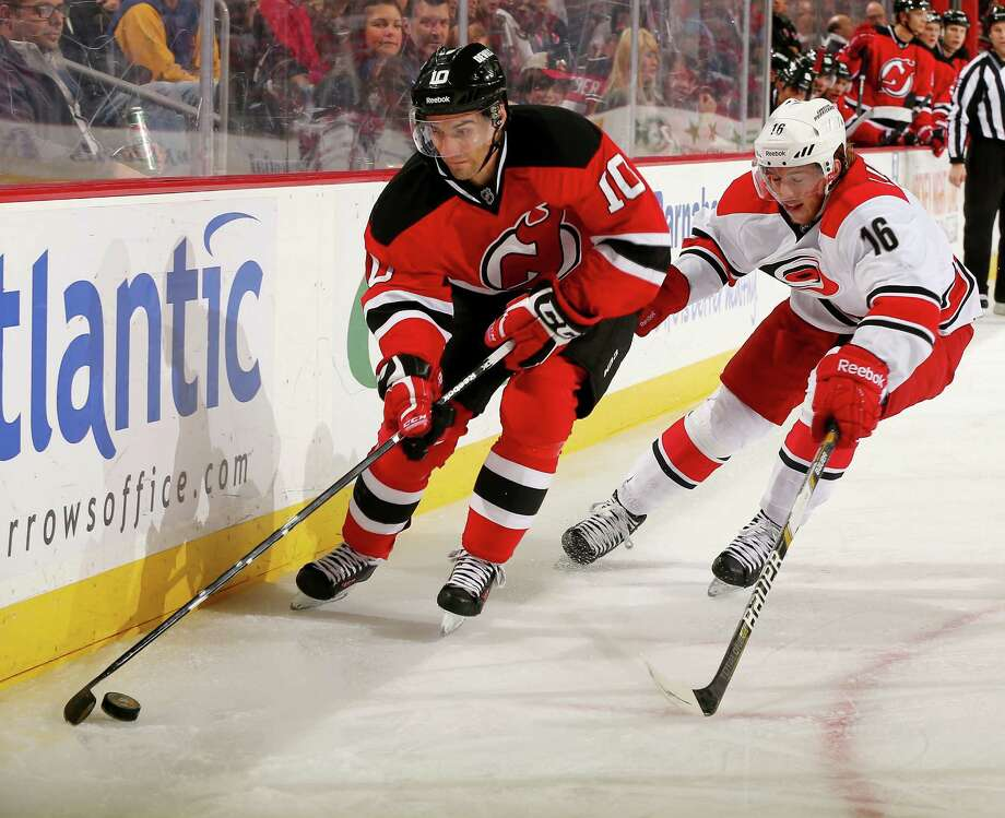 NEWARK, NJ - NOVEMBER 27:  Peter Harrold #10 of the New Jersey Devils tries to keep the puck from Elias Lindholm #16 of the Carolina Hurricanes at Prudential Center on November 27, 2013 in Newark, New Jersey.  (Photo by Elsa/Getty Images) ORG XMIT: 181111247 Photo: Elsa / 2013 Getty Images